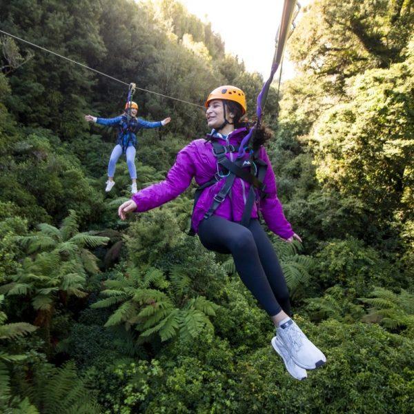 Woman on a zipline through native forest in Rotorua New Zealand