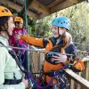 Instructor giving instructions to an adventurer before going on zipline through forest
