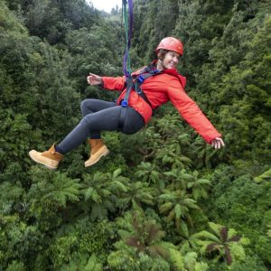 Woman in a red jacket zipping through native forest on a zipline in Rotorua New Zealand